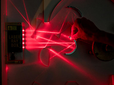 A hand interacting with a red laser experiment