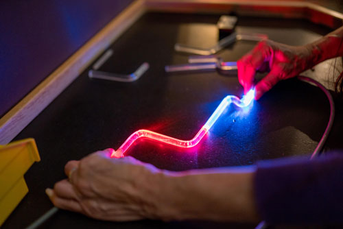 Hands holding a multi color lit tube